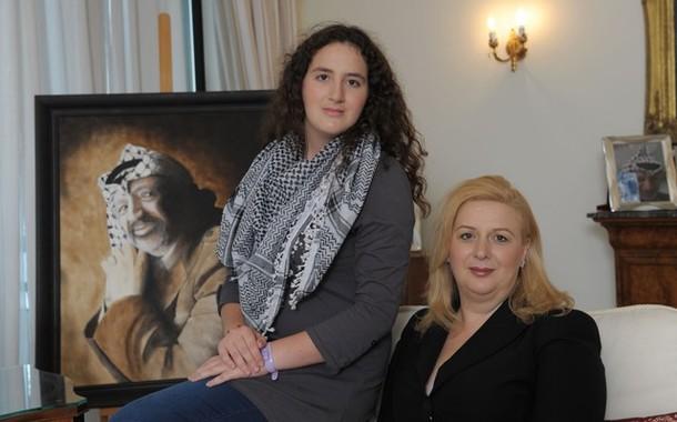 Suha Arafat posa con la figlia Zahwa Arafat  di fronte a un ritratto di suo marito defunto Yasser Arafat nella sua casa di Malta il 10 novembre 2011, alla vigilia del settimo anniversario della sua morte. Arafat è morto il 11 Novembre 2004 in un ospedale francese. Un tribunale tunisino ha emesso un mandato di arresto internazionale contro la vedova del defunto leader palestinese Yasser Arafat per presunta corruzione, un ufficiale giudiziario ha dichiarato il 31 ottobre. Suha Arafat, che è stata privata della sua cittadinanza tunisina nel 2007 a seguito di un contenzioso con l'ex famiglia regnante tunisina , attualmente vive a Malta, ha negato con veemenza le accuse di corruzione e si è detta pronta a deporre mettendo il caso a nudo.