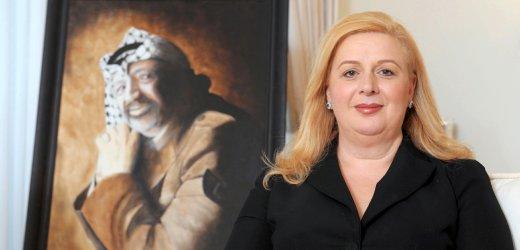 Suha Arafat posa di fronte a un ritratto di suo marito defunto Yasser Arafat nella sua casa di Malta il 10 novembre 2011, alla vigilia del settimo anniversario della sua morte.