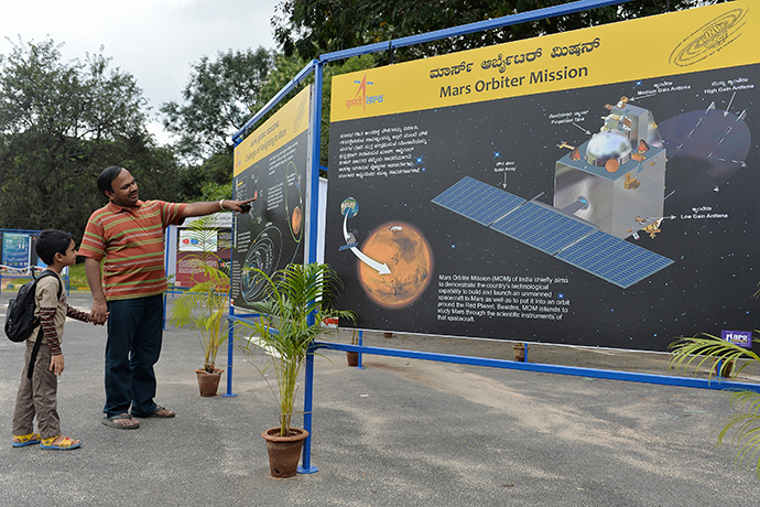 Padre e figlio guardano le informazioni relative alla missione sul pianeta Marte su di un manifesto esposto a Nehru Planetarium in anteprima speciale della missione inaugurale su Marte dell'Orbiter Mission indiana, a Bangalore il 23 settembre 2014