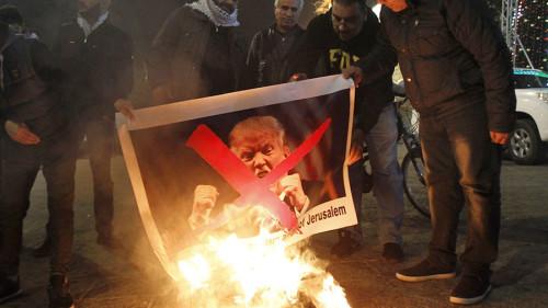 I manifestanti palestinesi bruciano le immagini del presidente degli Stati Uniti Donald Trump nella piazza della mangiatoia a Betlemme il 5 dicembre 2017