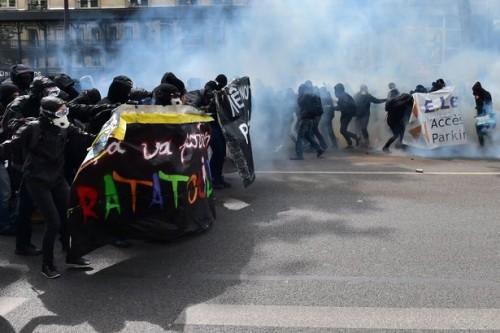 La gente tiene gli striscioni di protesta mentre marcia tra il fumo dei lacrimogeni durante gli scontri di Parigi