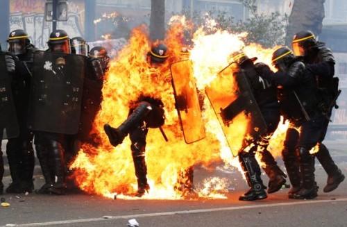 Un agente della Gendarmerie è completamente circondato dalle fiamme, mentre la violenza aumenta